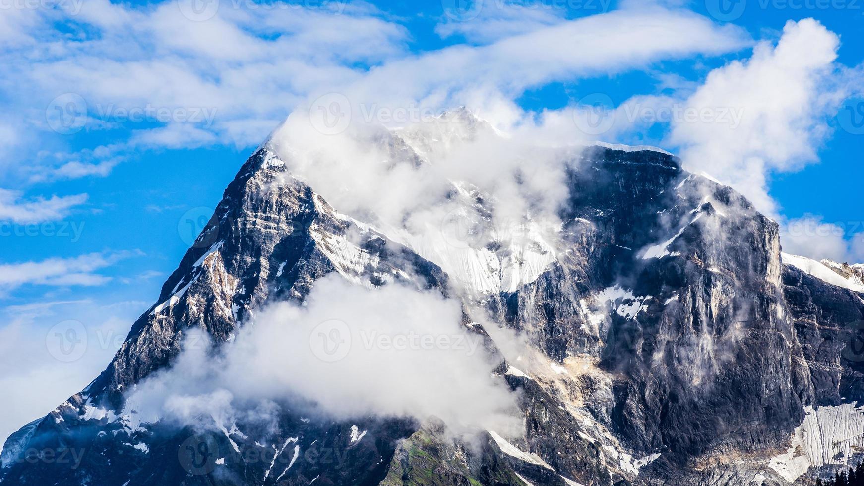 pico da montanha de neve com nuvens no céu azul foto