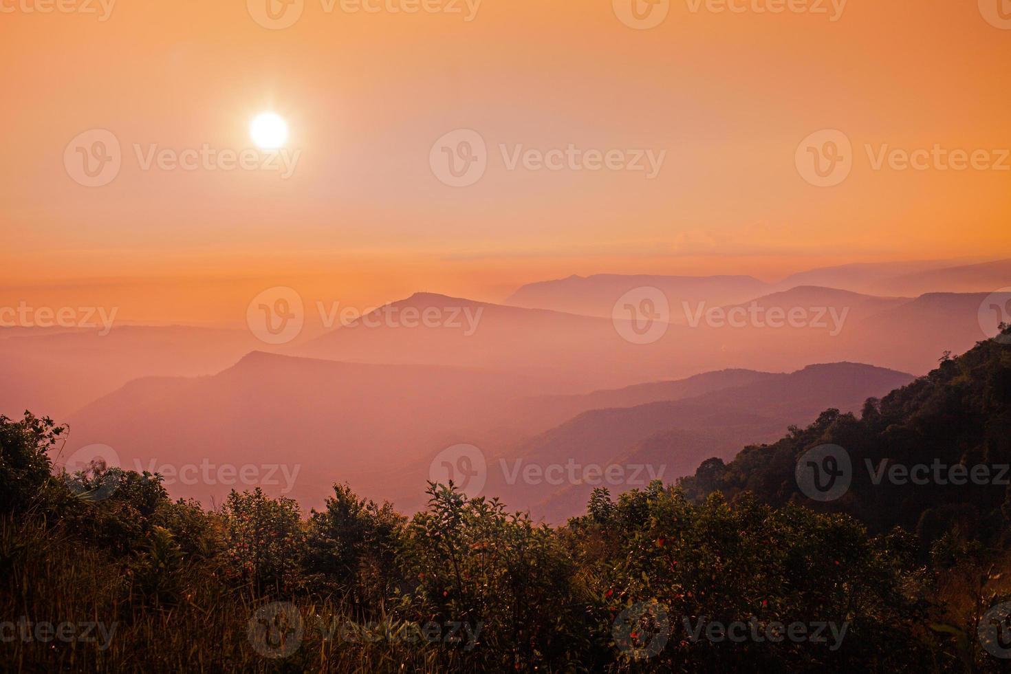 nascer do sol sobre a névoa e a montanha foto