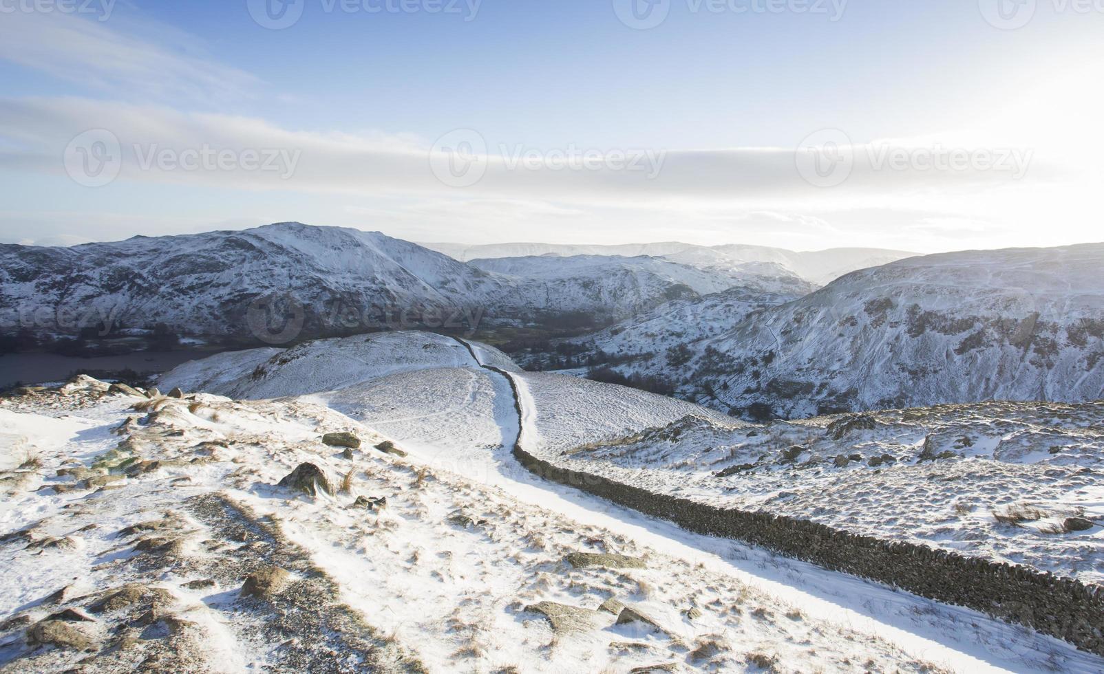 longo caminho coberto de neve e parede que leva às montanhas foto
