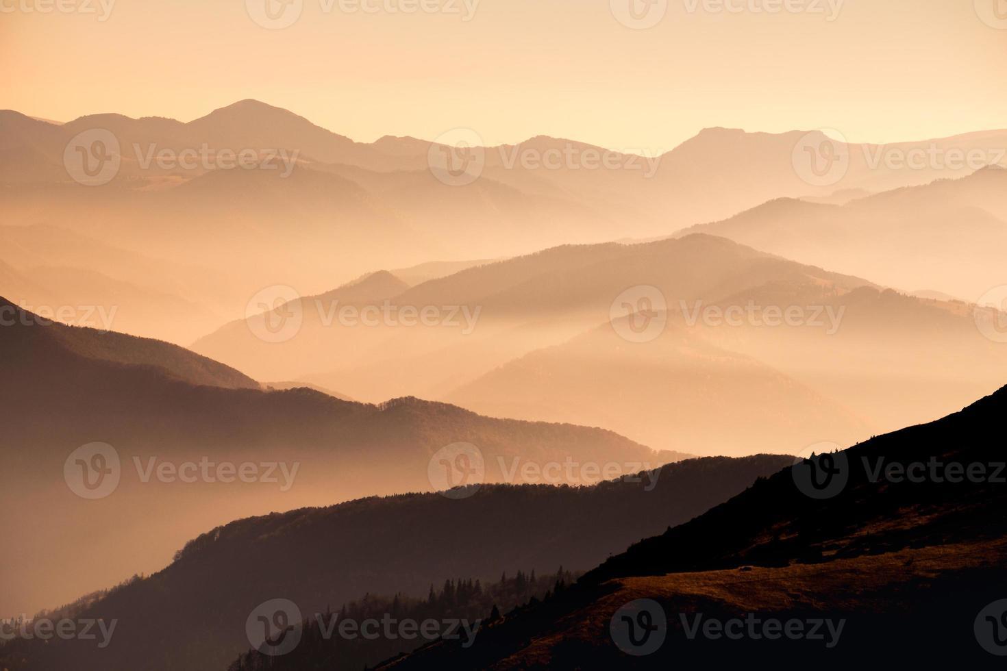 vista da paisagem das montanhas enevoadas ao pôr do sol foto