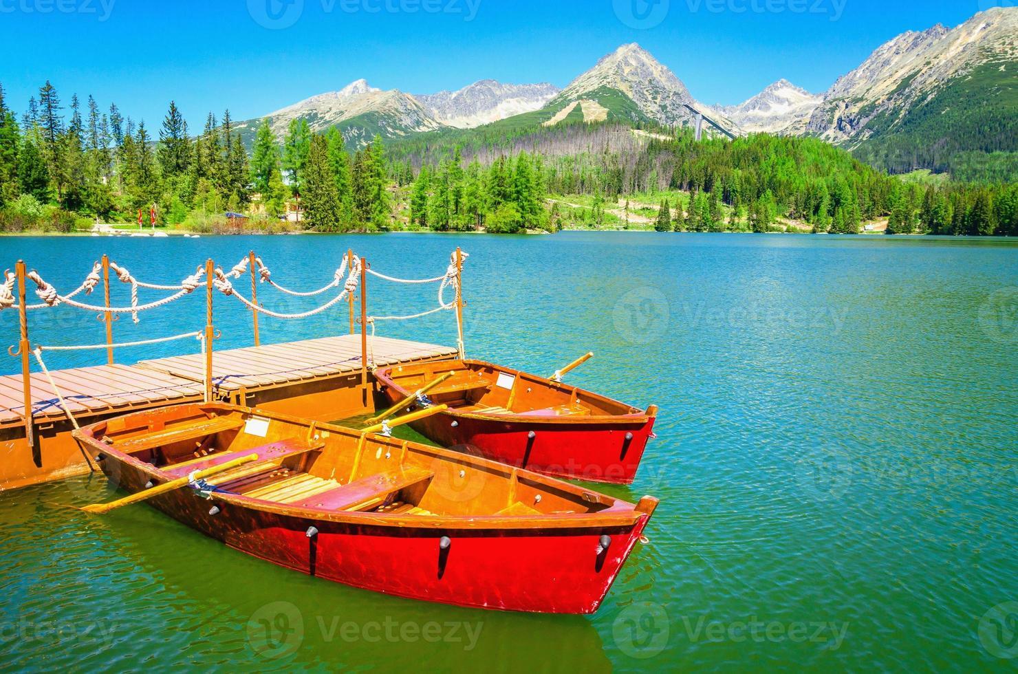 barcos de madeira vermelhos no lago da montanha na Eslováquia foto