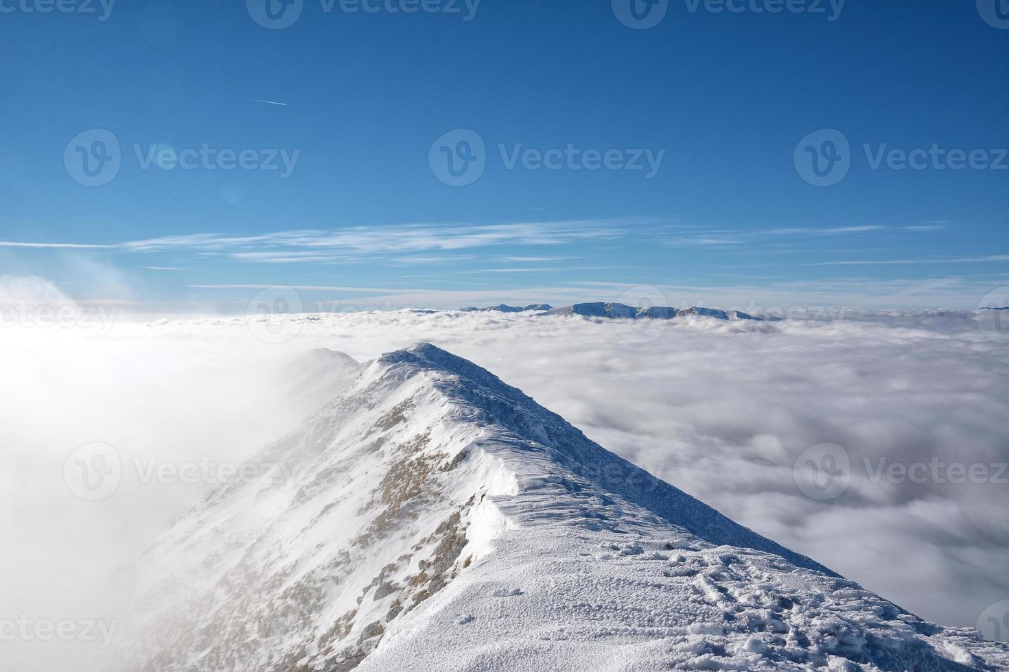 paisagem alpina com picos cobertos por neve e nuvens foto
