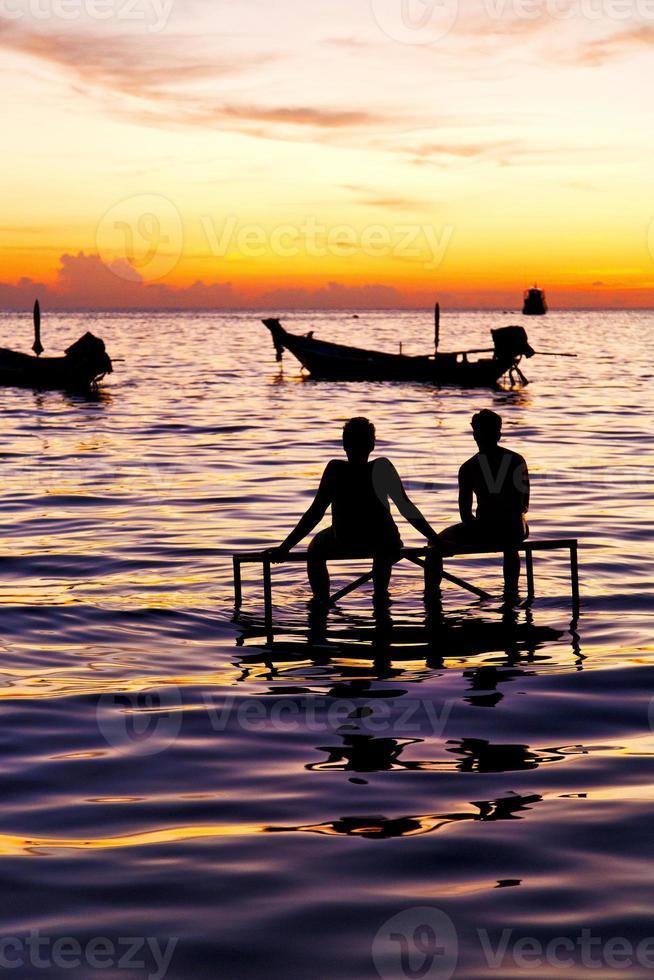 barco ao nascer do sol e água na costa sul da tailândia foto