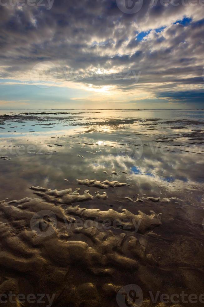 reflexo do céu dramático na praia de nusa dua, bali, indonésia foto