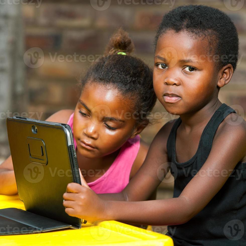duas meninas africanas sentadas à mesa com o tablet. foto