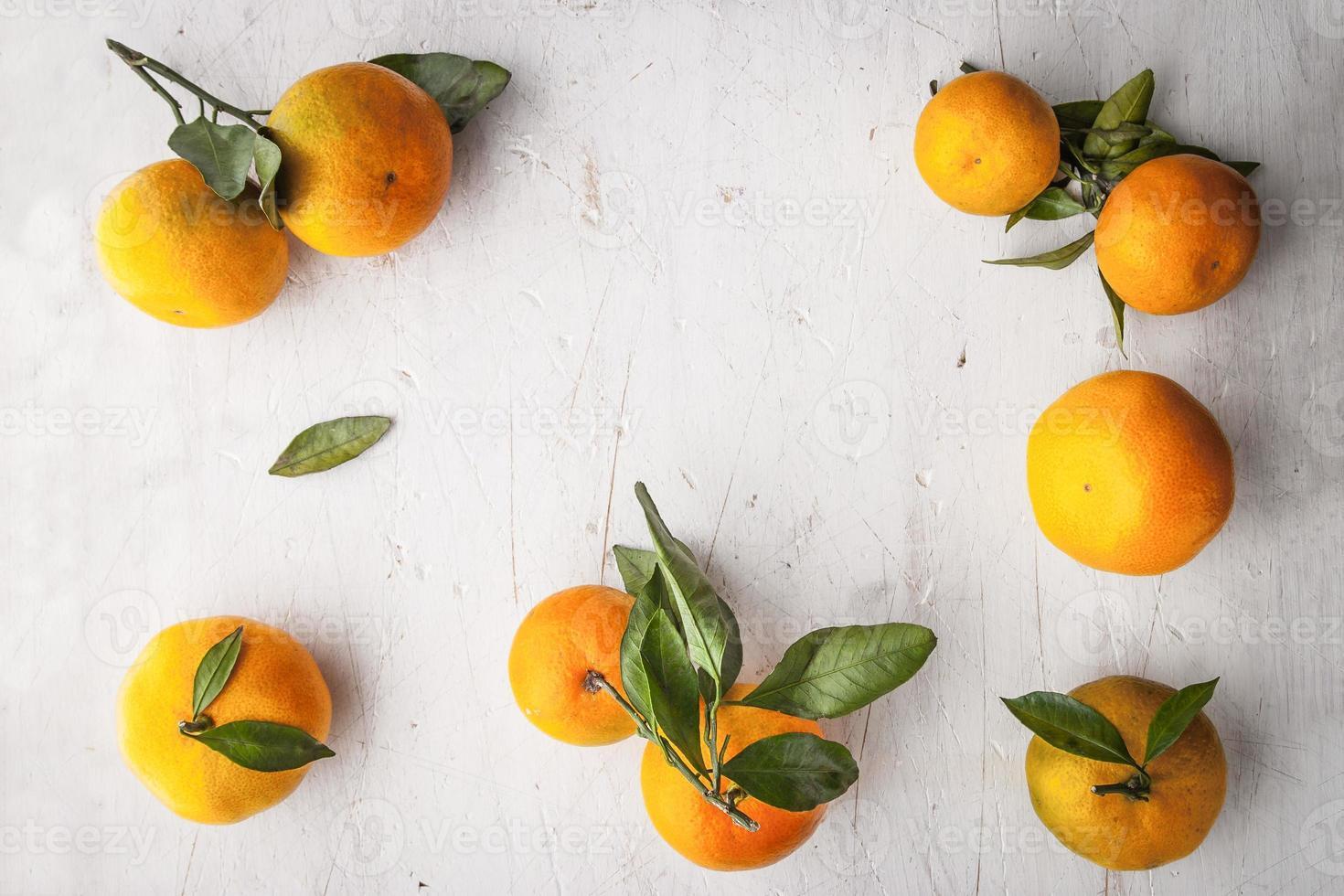 moldura de tangerinas na mesa de madeira branca horizontal foto