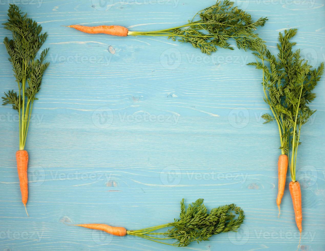 composição de cenouras em um fundo azul de madeira foto