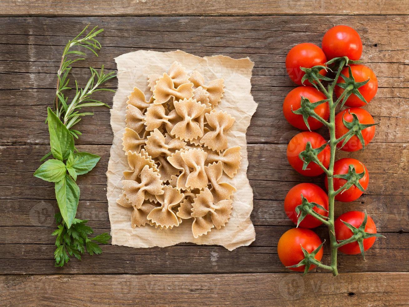 macarrão, tomate e ervas em fundo de madeira foto