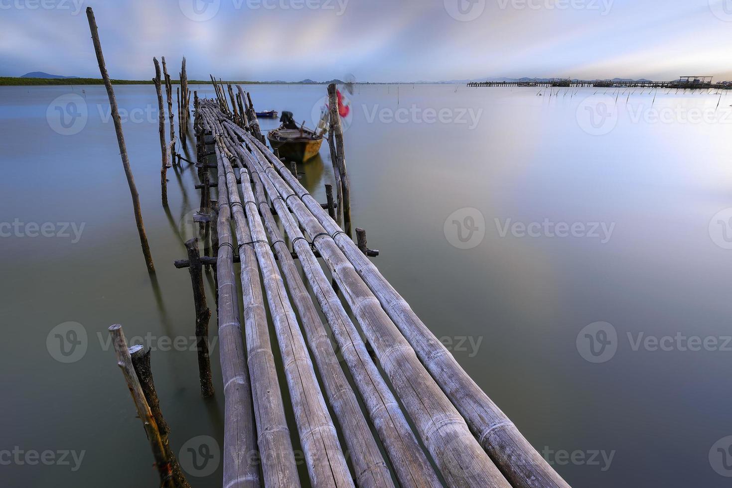ponte de bambu que se estende até o mar. foto