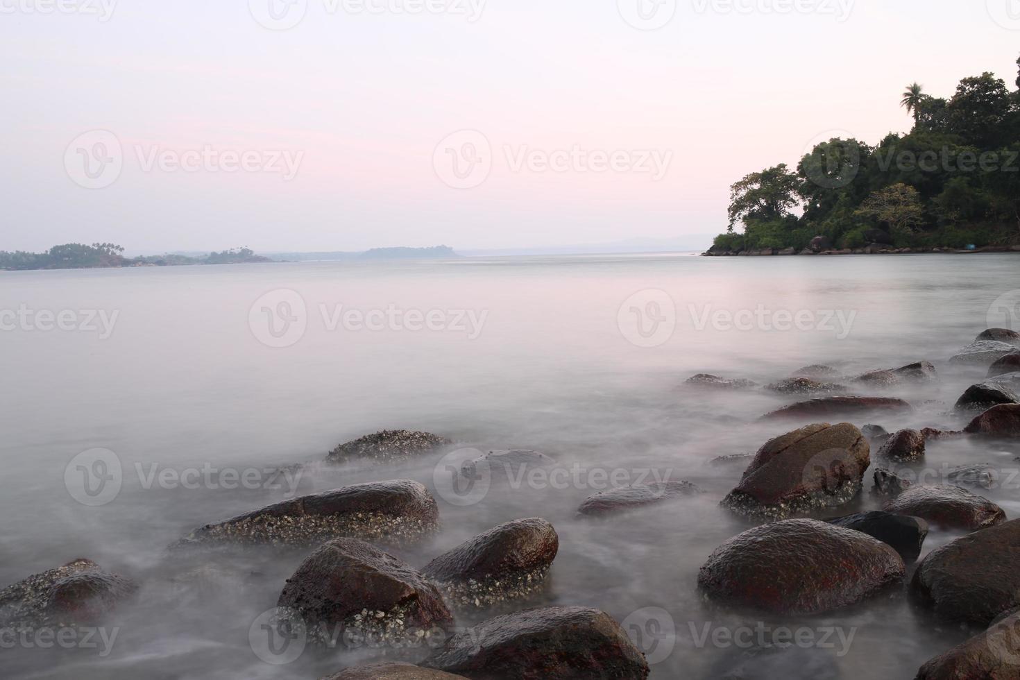 bela praia da província de goa no pôr do sol com pedras em foto