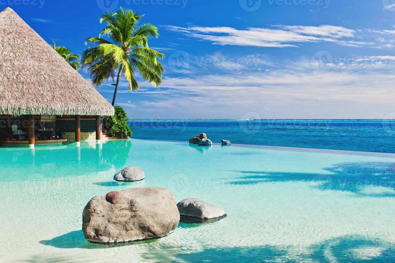 uma piscina infinita com praia artificial e oceano azul foto