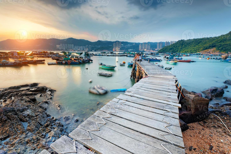 longo caminho de madeira em aldeia de pesca ao pôr do sol foto