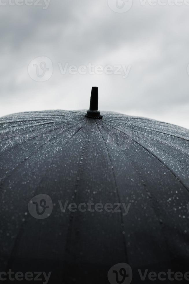 uma imagem de chuva batendo em um guarda-chuva preto foto
