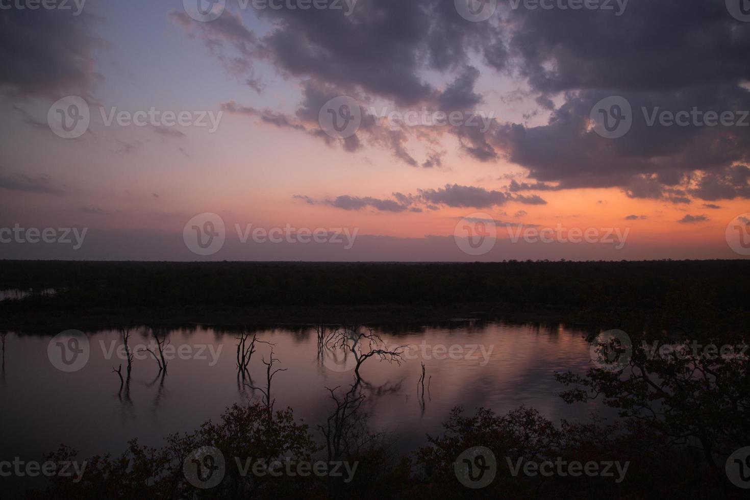 pôr do sol sobre um lago em Kruger foto