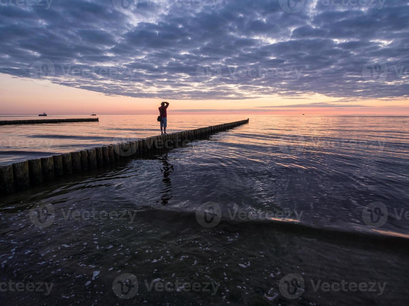 fotógrafo em um quebra-mar foto
