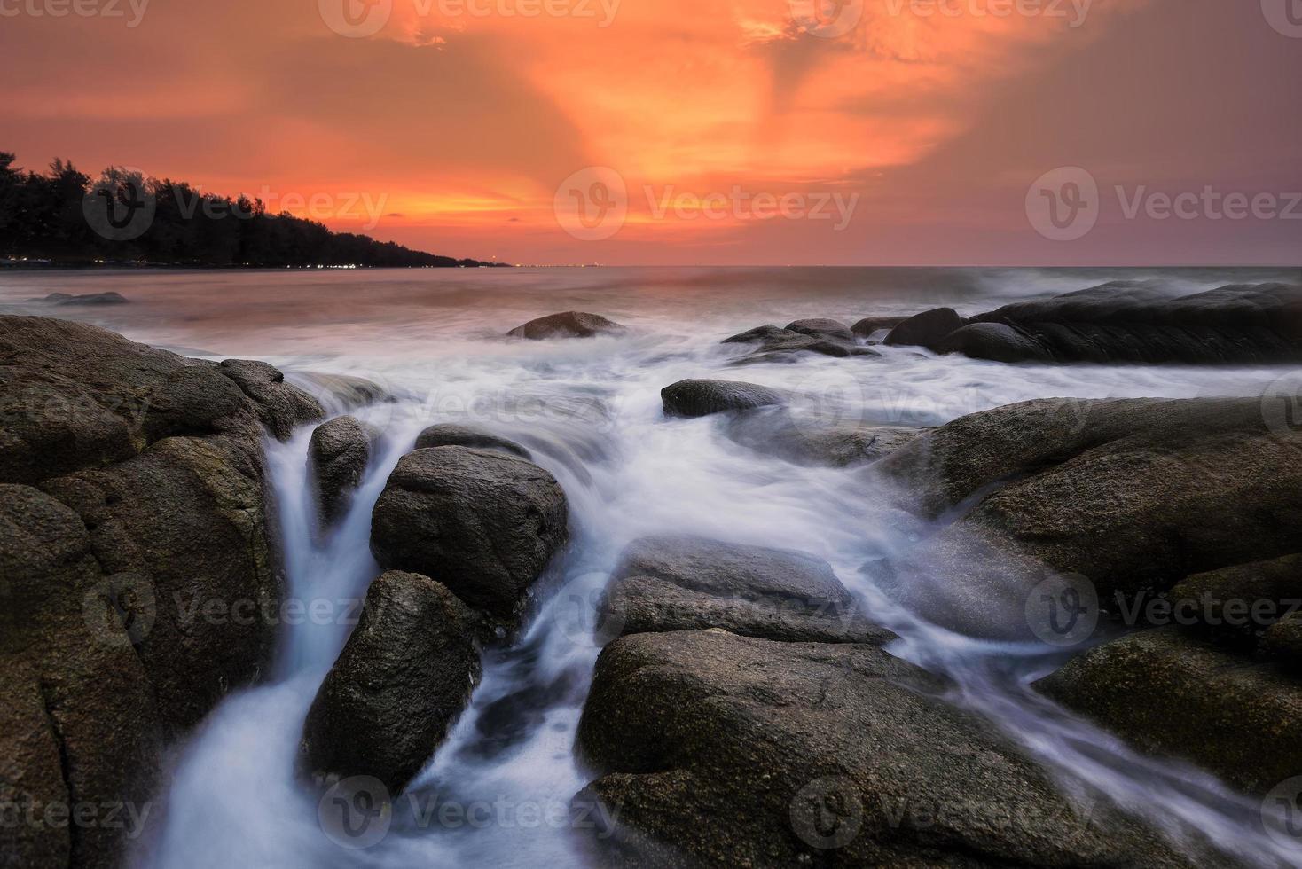 noite luz pôr do sol ondas do mar espirrando pedras foto