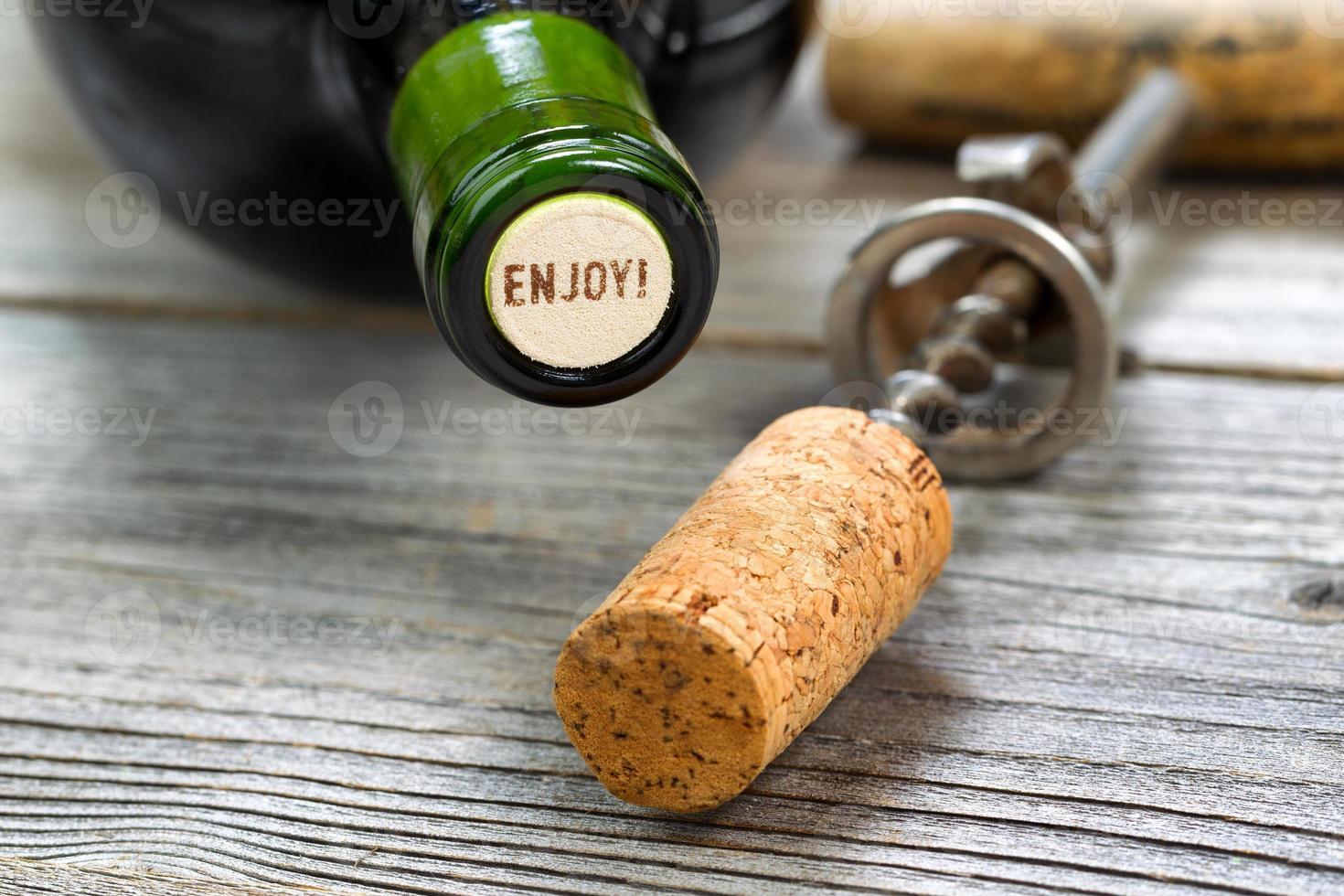 garrafa de vinho tinto fechada com abridor no fundo foto