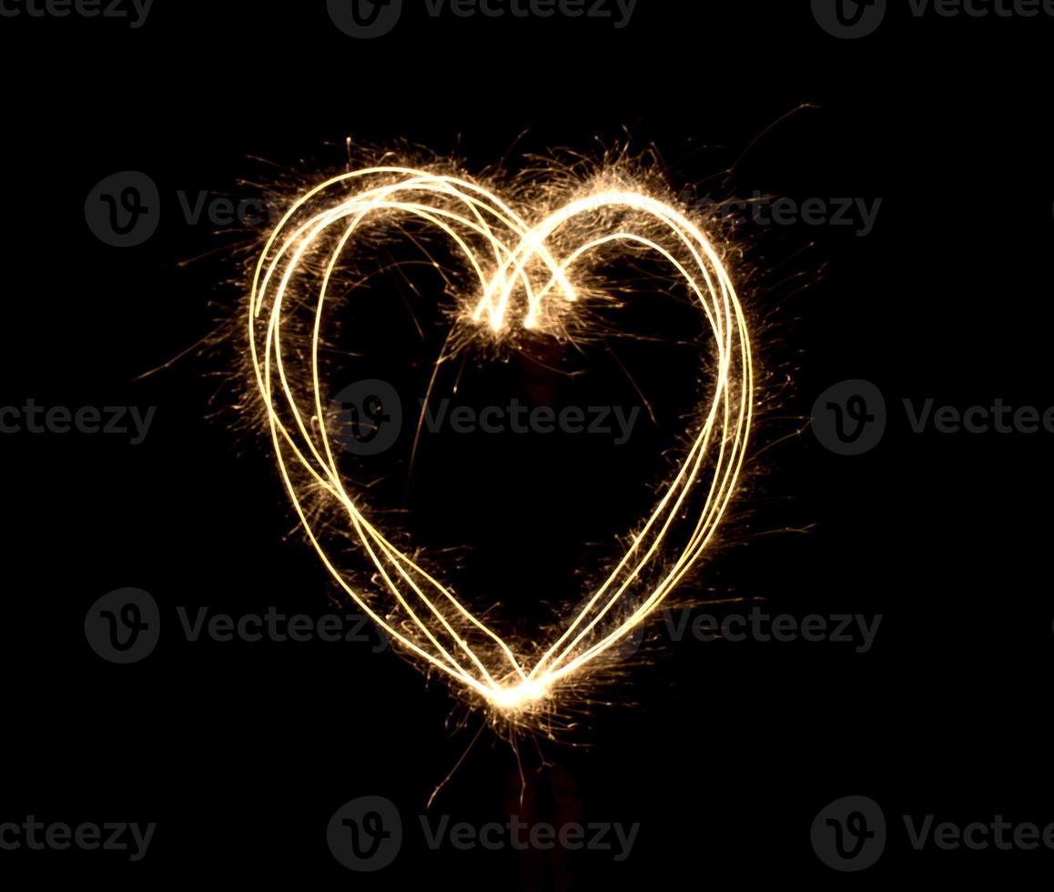 formato de coração à noite por fogos de artifício foto