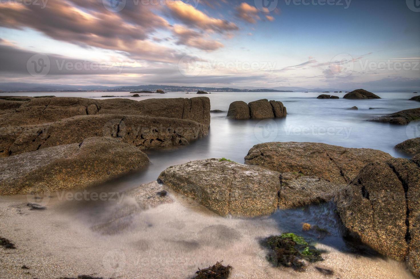 água entre as rochas de uma praia foto