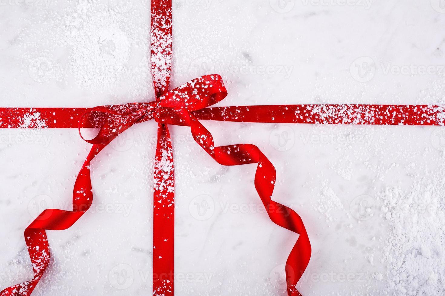 Tábua de confeitaria de mármore envolta em fita vermelha com açúcar de confeiteiro foto