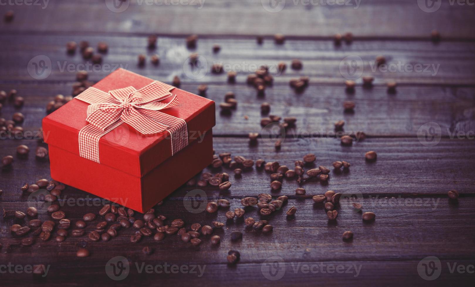 caixa de presente vermelha e café na mesa de madeira. foto