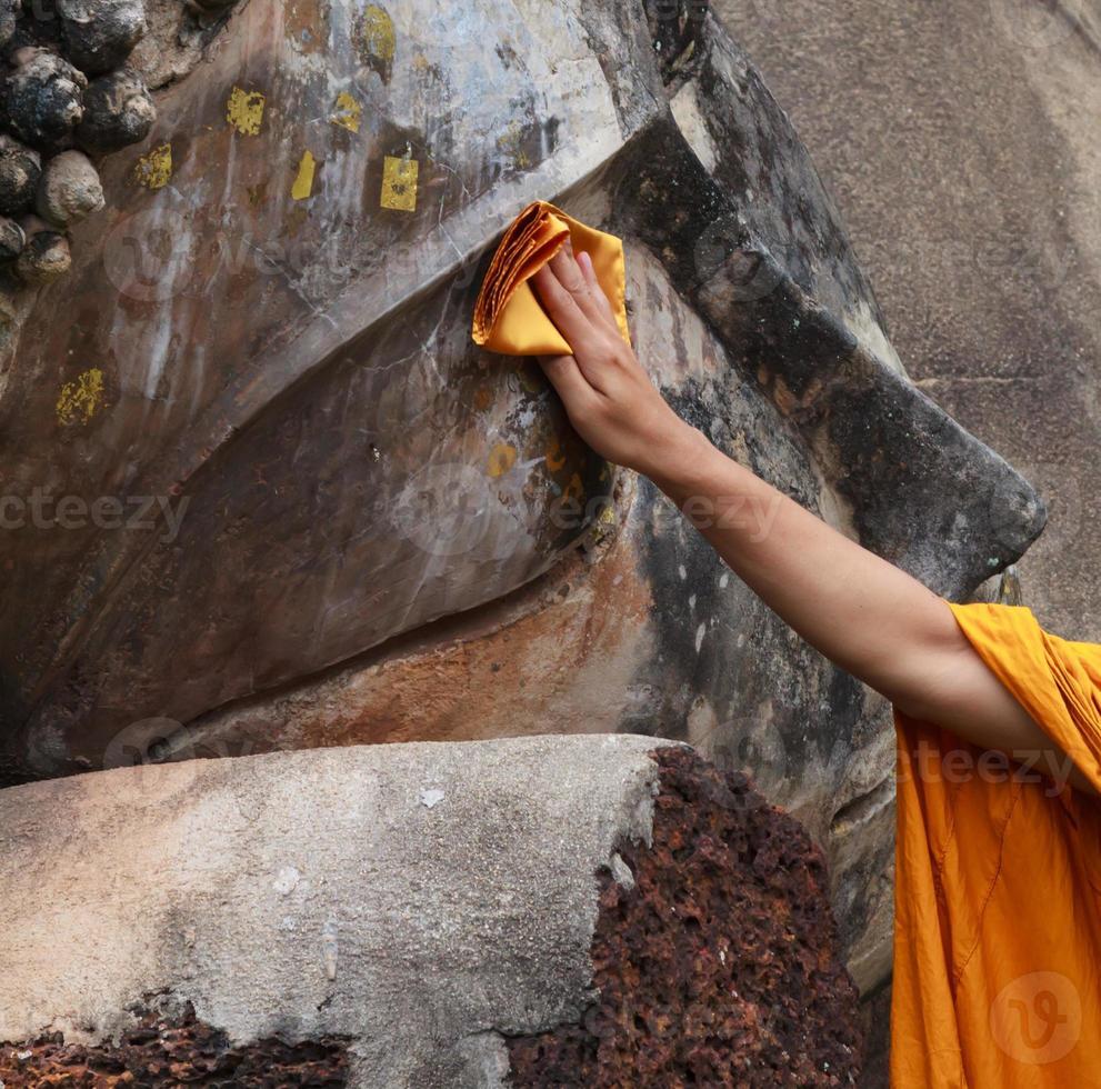monge está limpando estátua de Buda foto