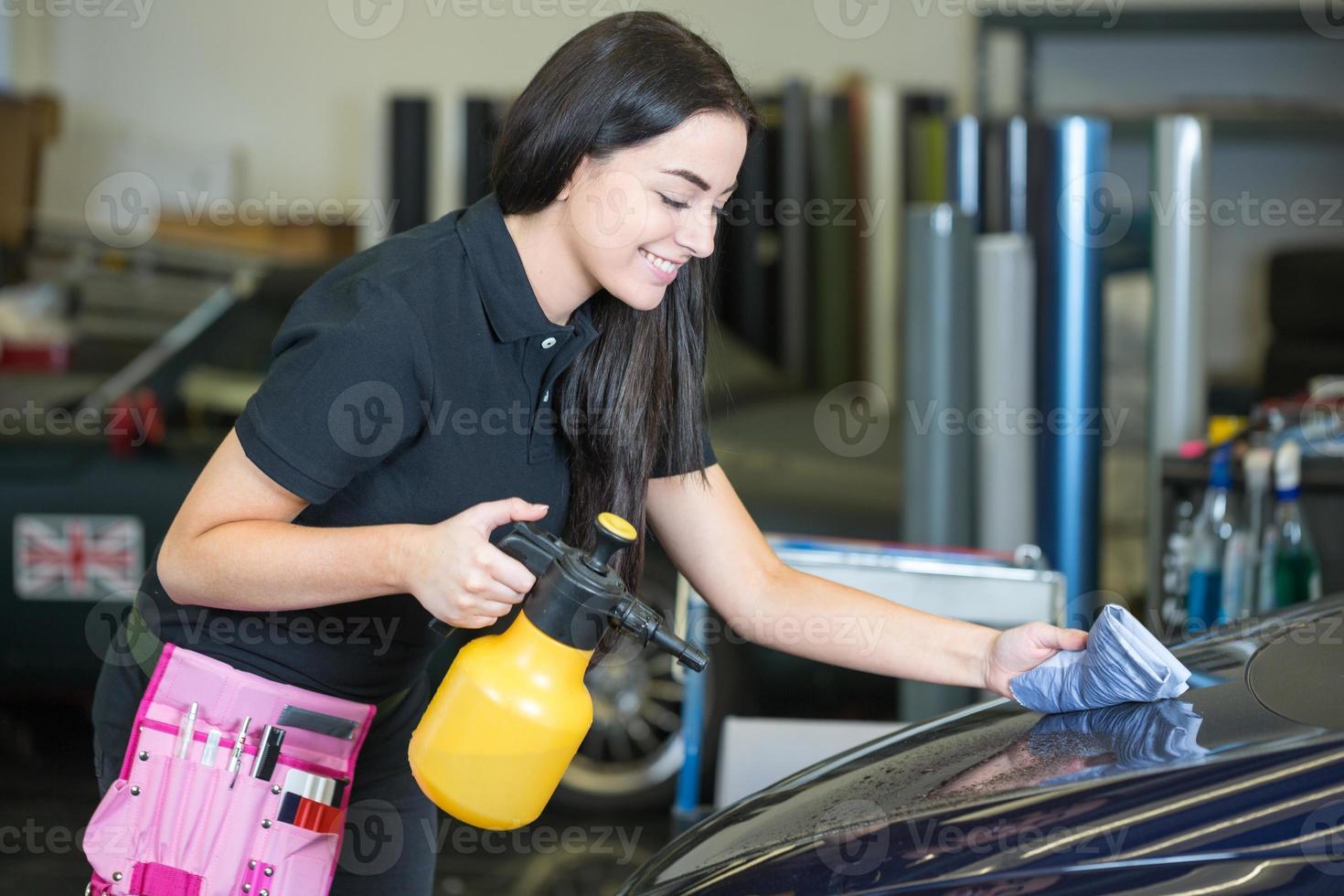 trabalhador limpando carro com pano e spray foto