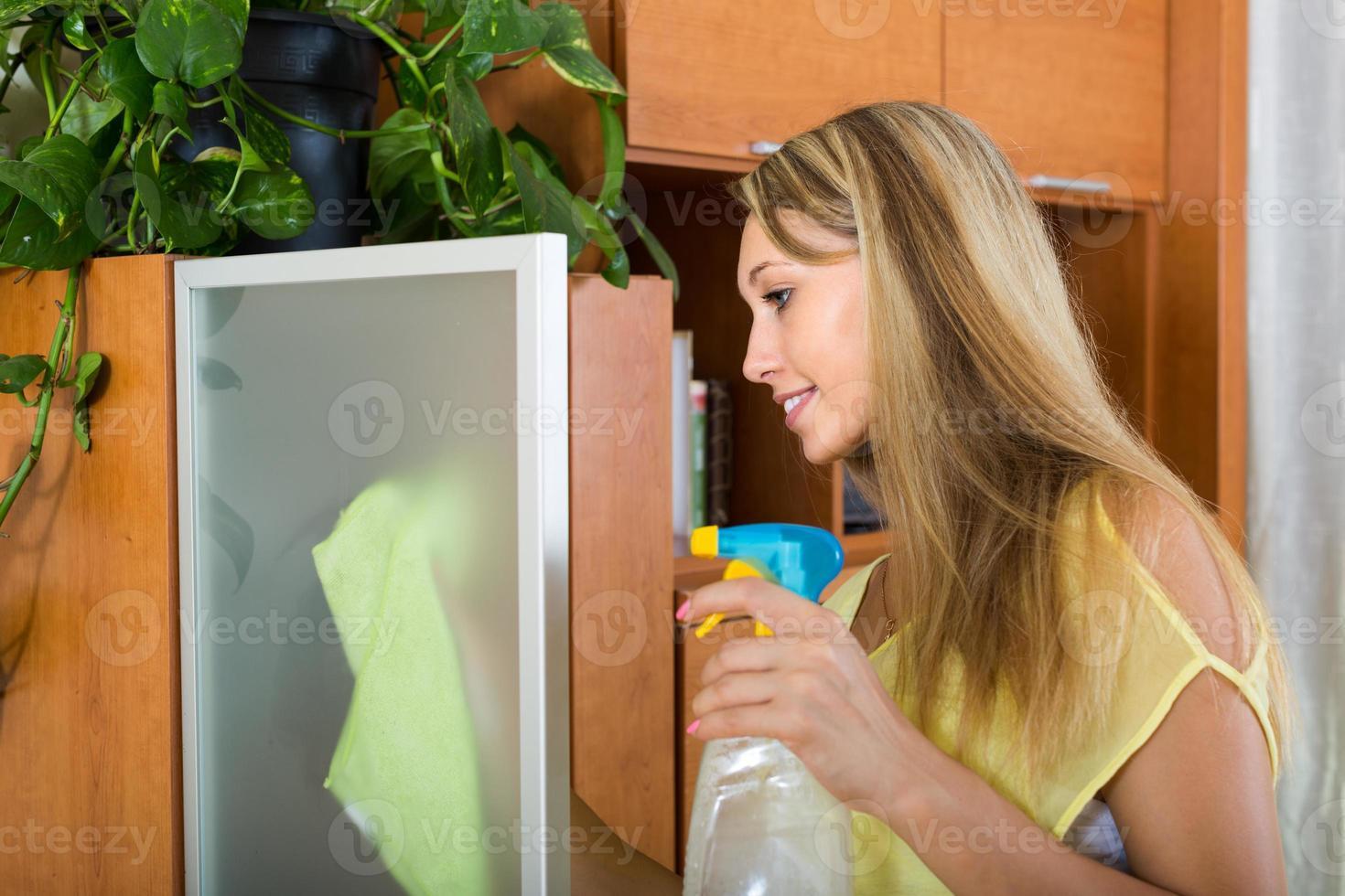 mulher loira limpando vidro foto