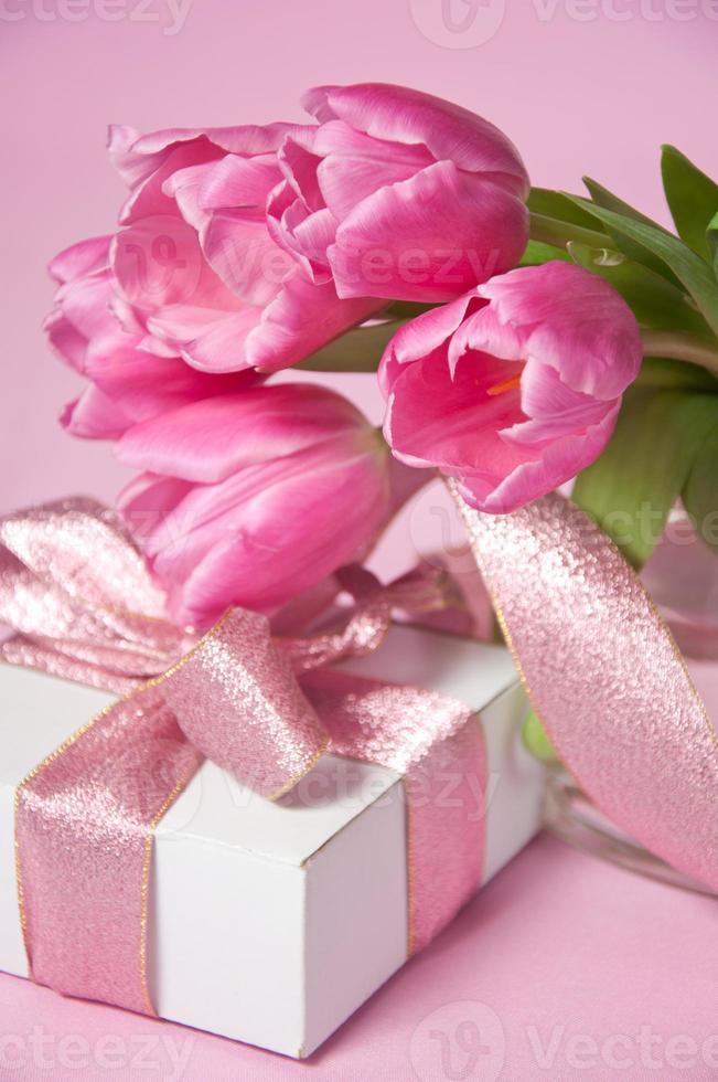 tulipas rosa em um vaso com a caixa de presente foto