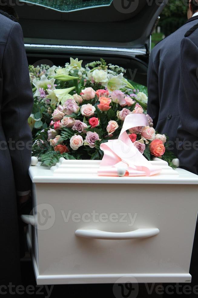 caixão branco em um carro funerário cinza foto