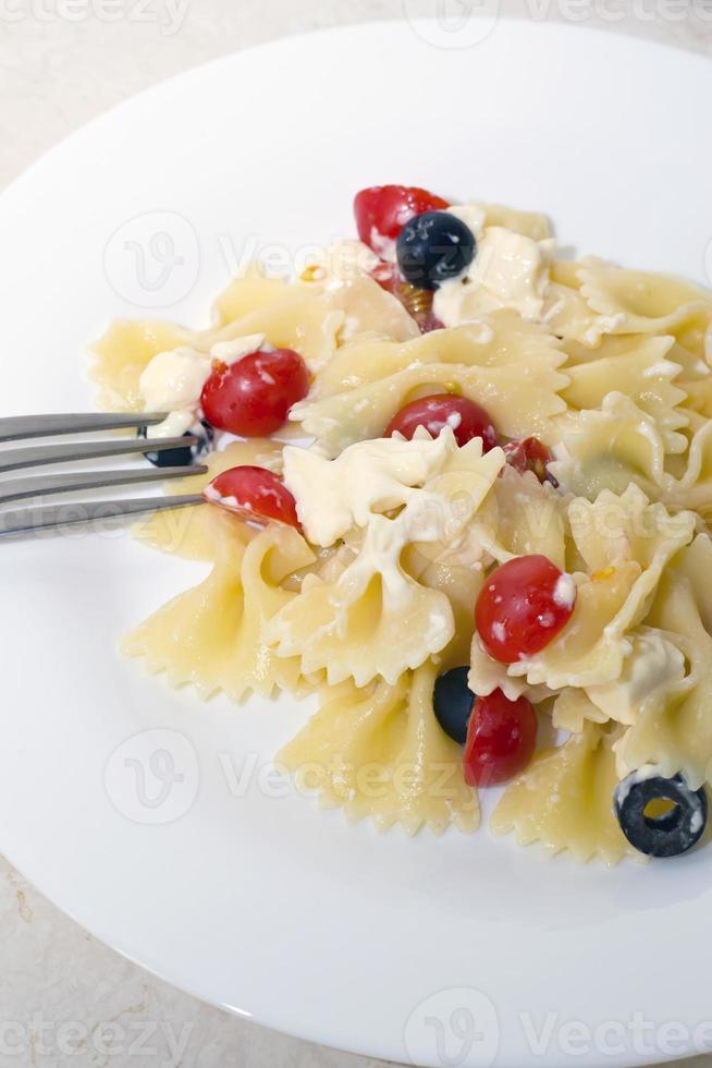 fitas de macarrão, tomate cereja e azeitonas foto