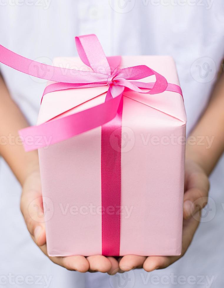 menino mão dá caixa de presente rosa foto