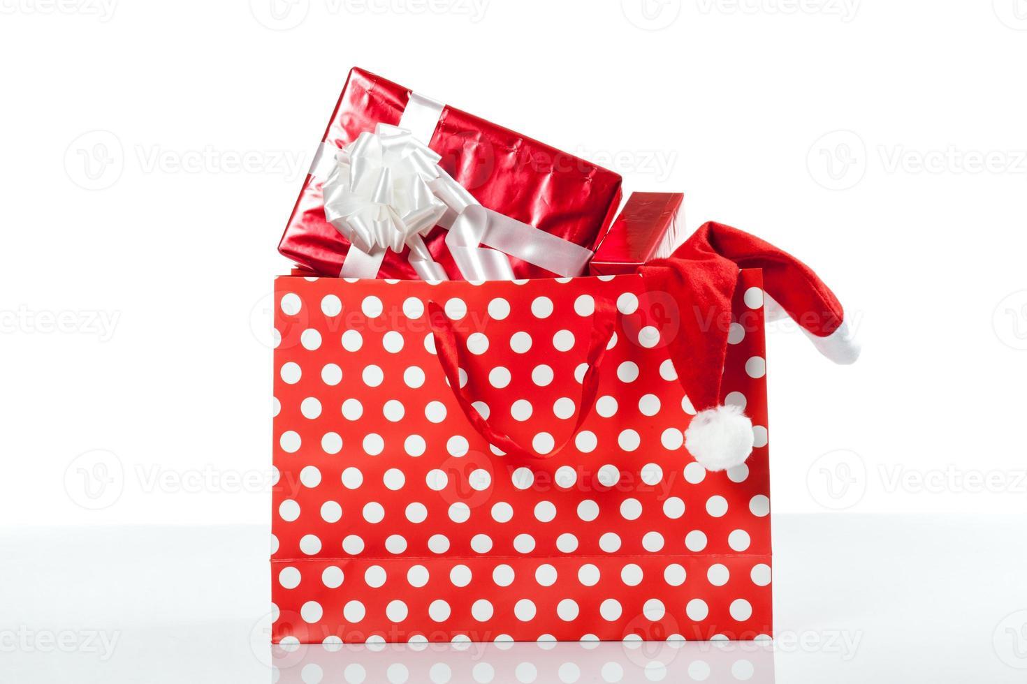 caixas de presente vermelhas e chapéu de natal em sacolas de compras foto