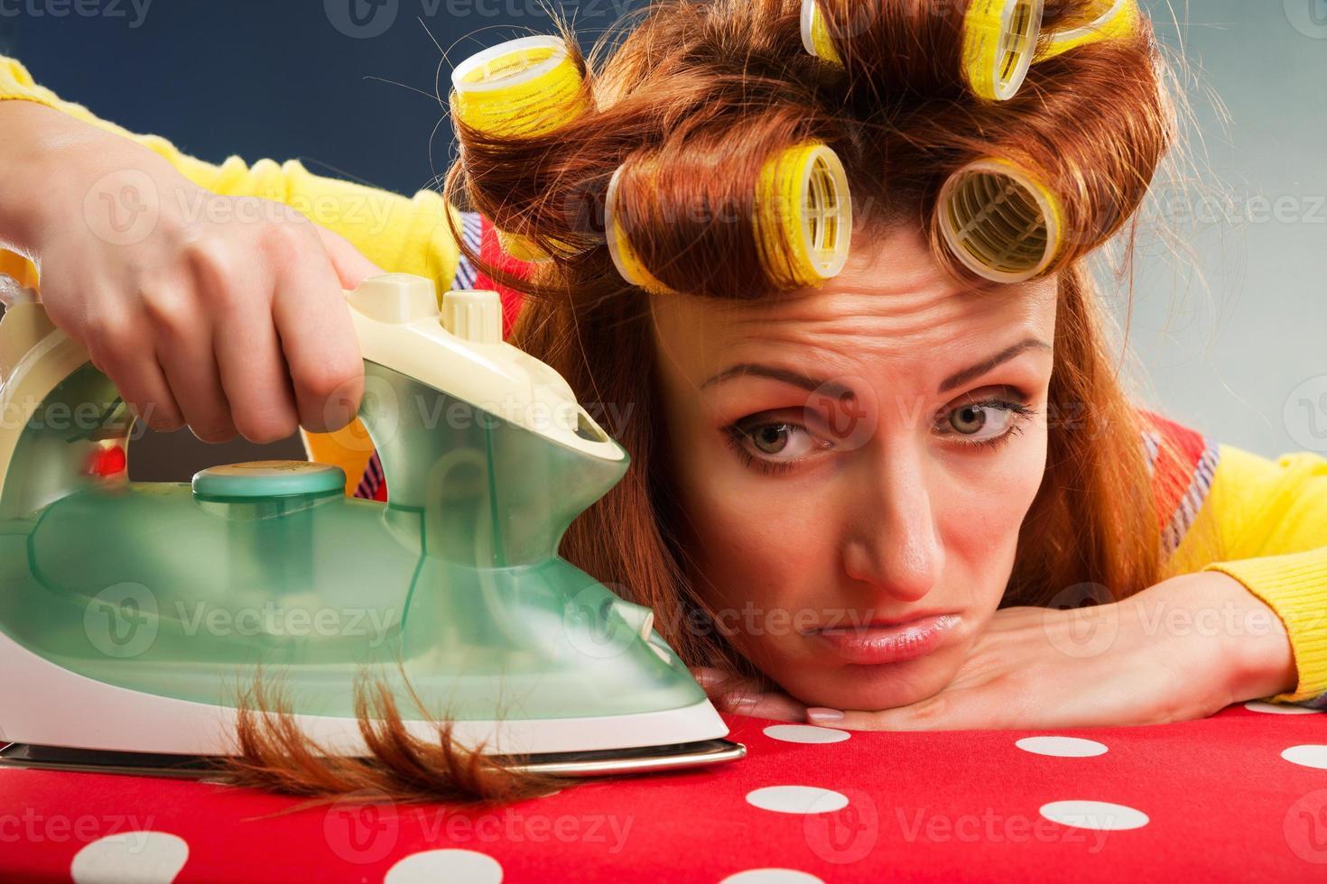 dona de casa cansada com tábua de passar foto