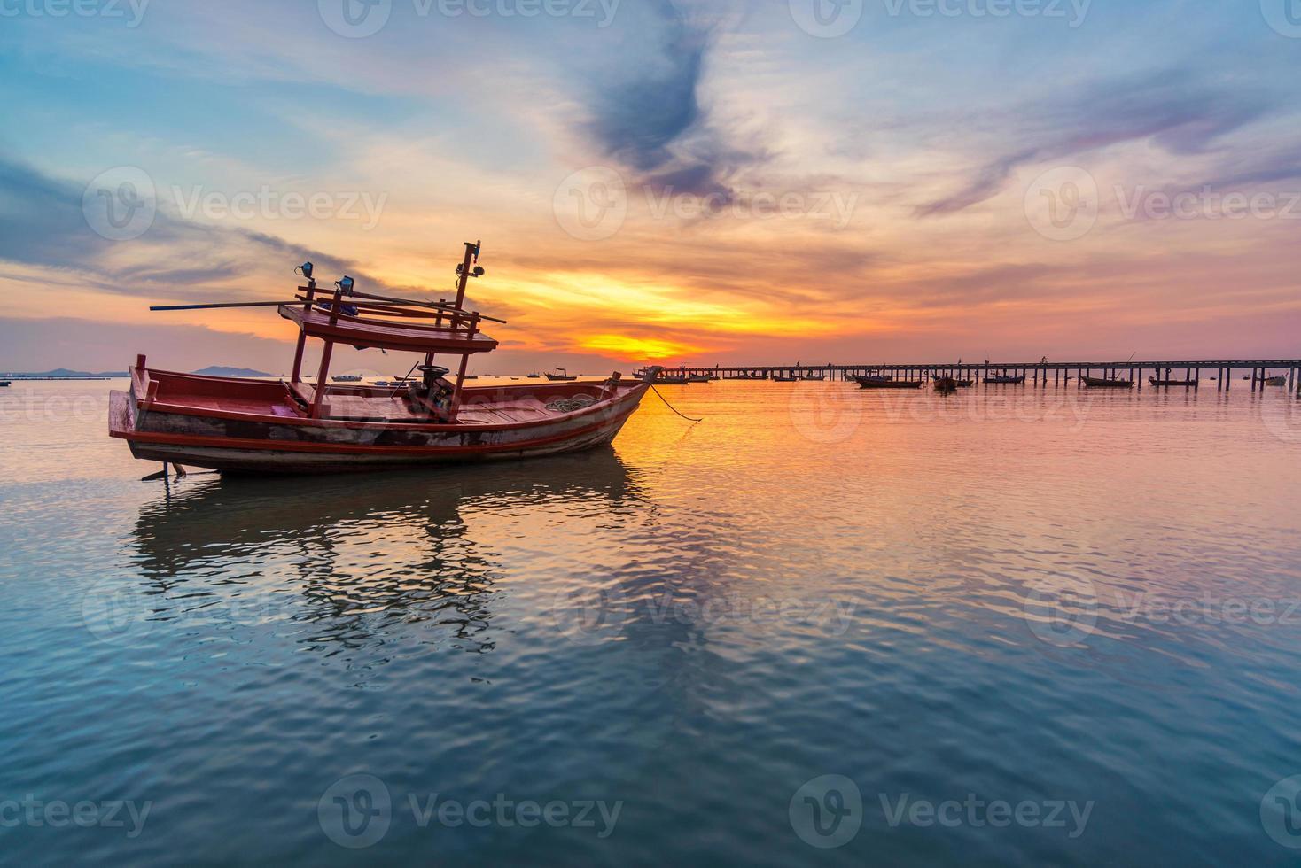 pôr do sol no mar e no barco foto