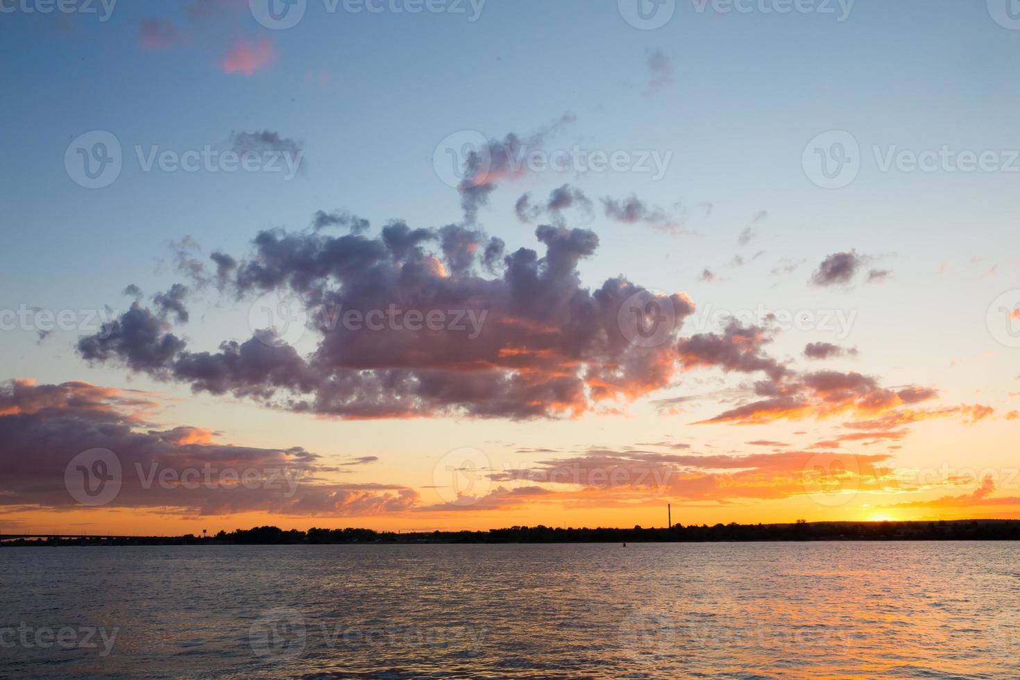 maravilhoso pôr do sol laranja e grande nuvem sobre o rio foto