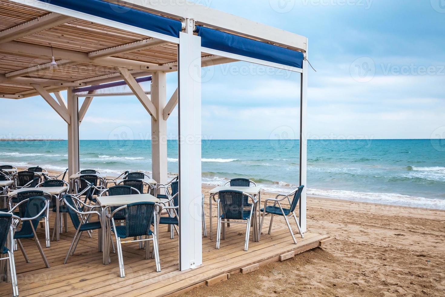 interior do bar do lado do mar com piso de madeira e poltronas de metal foto