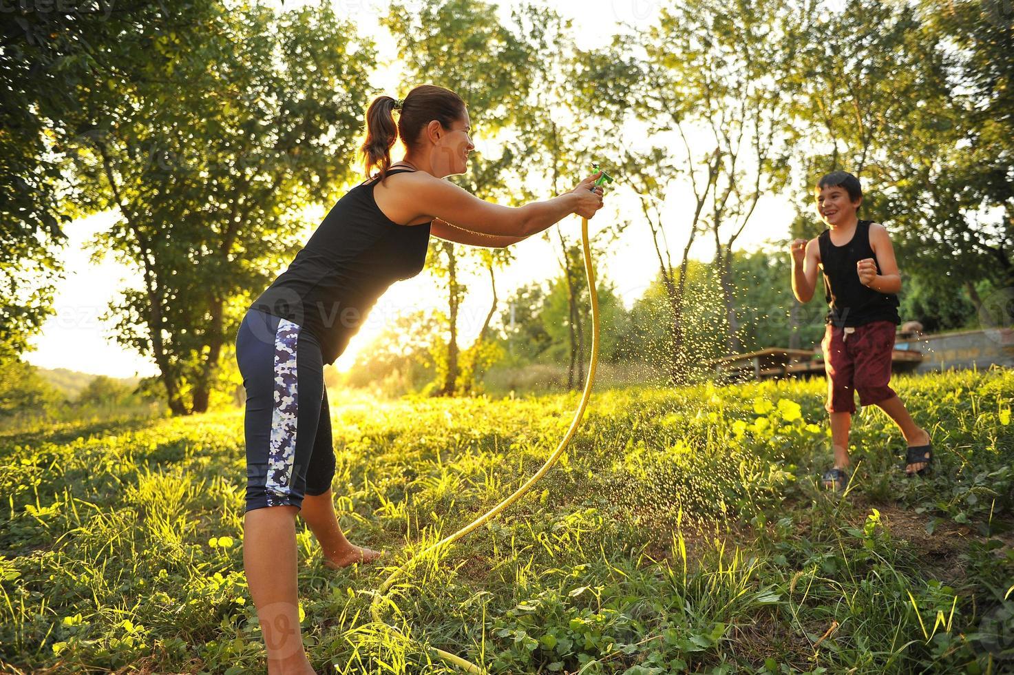 mãe e filho brincando no parque com água. foto
