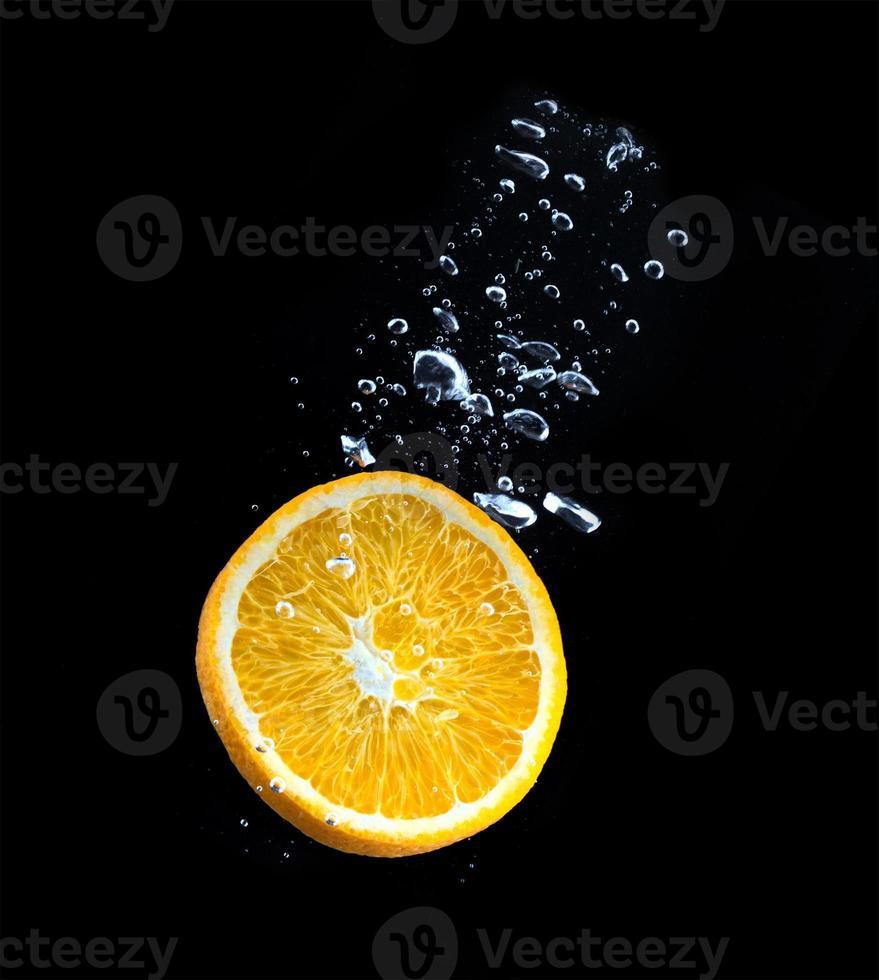 fatia de laranja na água com bolhas foto