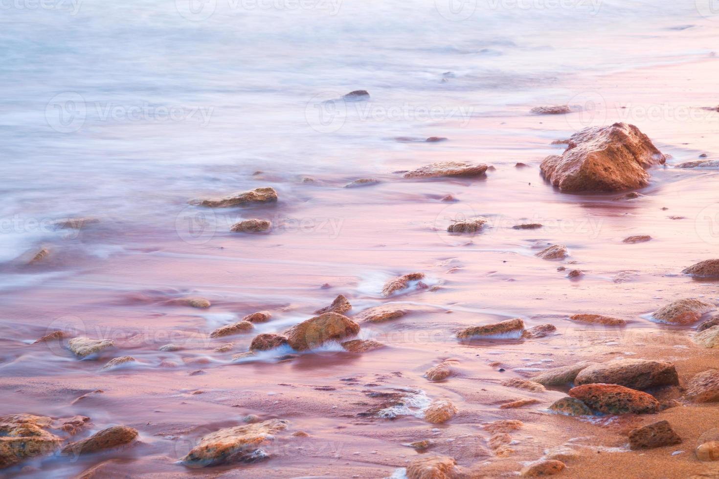 mar calmo e pedras ao nascer do sol foto