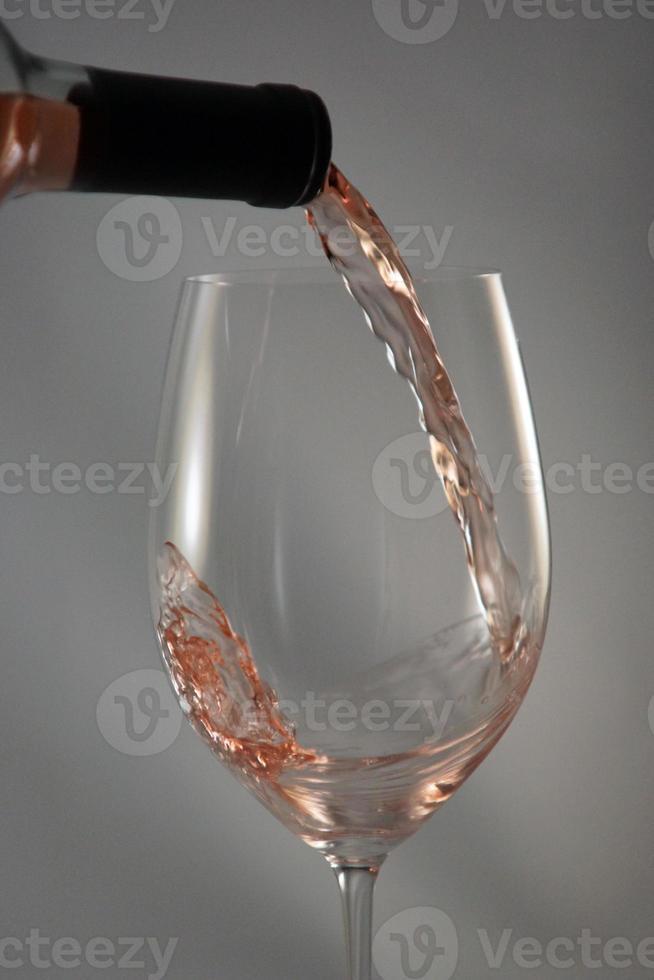 vinho rosado sendo derramado dentro de um copo foto