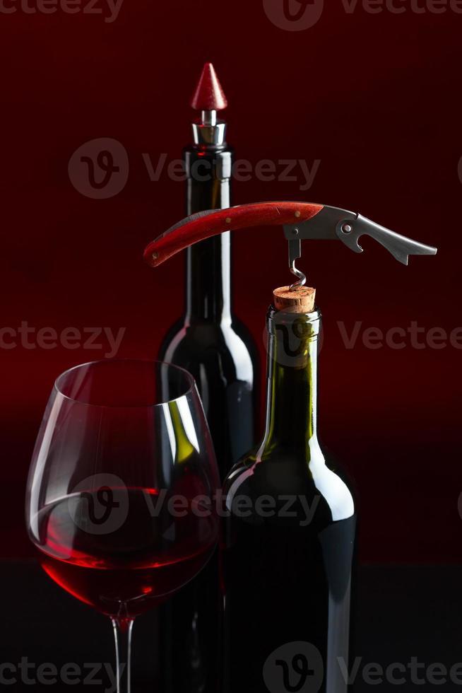 vinho tinto e saca-rolhas foto