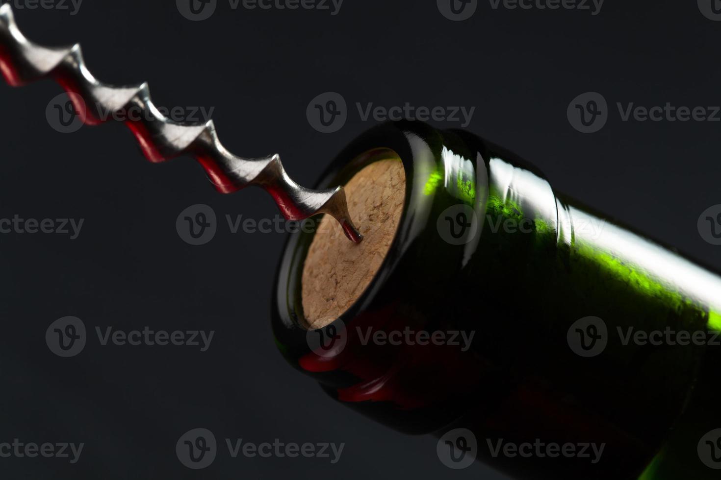 garrafa de vinho tinto e saca-rolhas foto