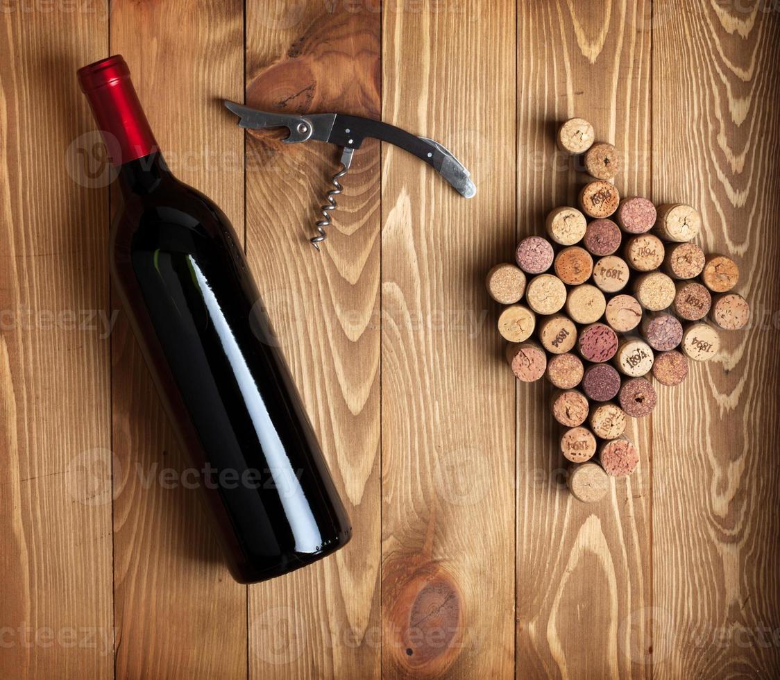 garrafa de vinho tinto, saca-rolhas e rolhas em forma de uva foto