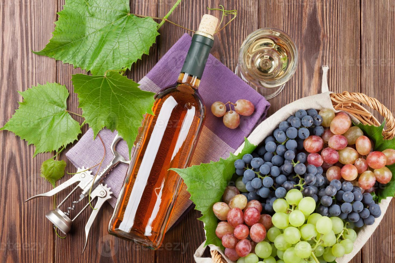 cacho de uvas, vinho branco e saca-rolhas foto