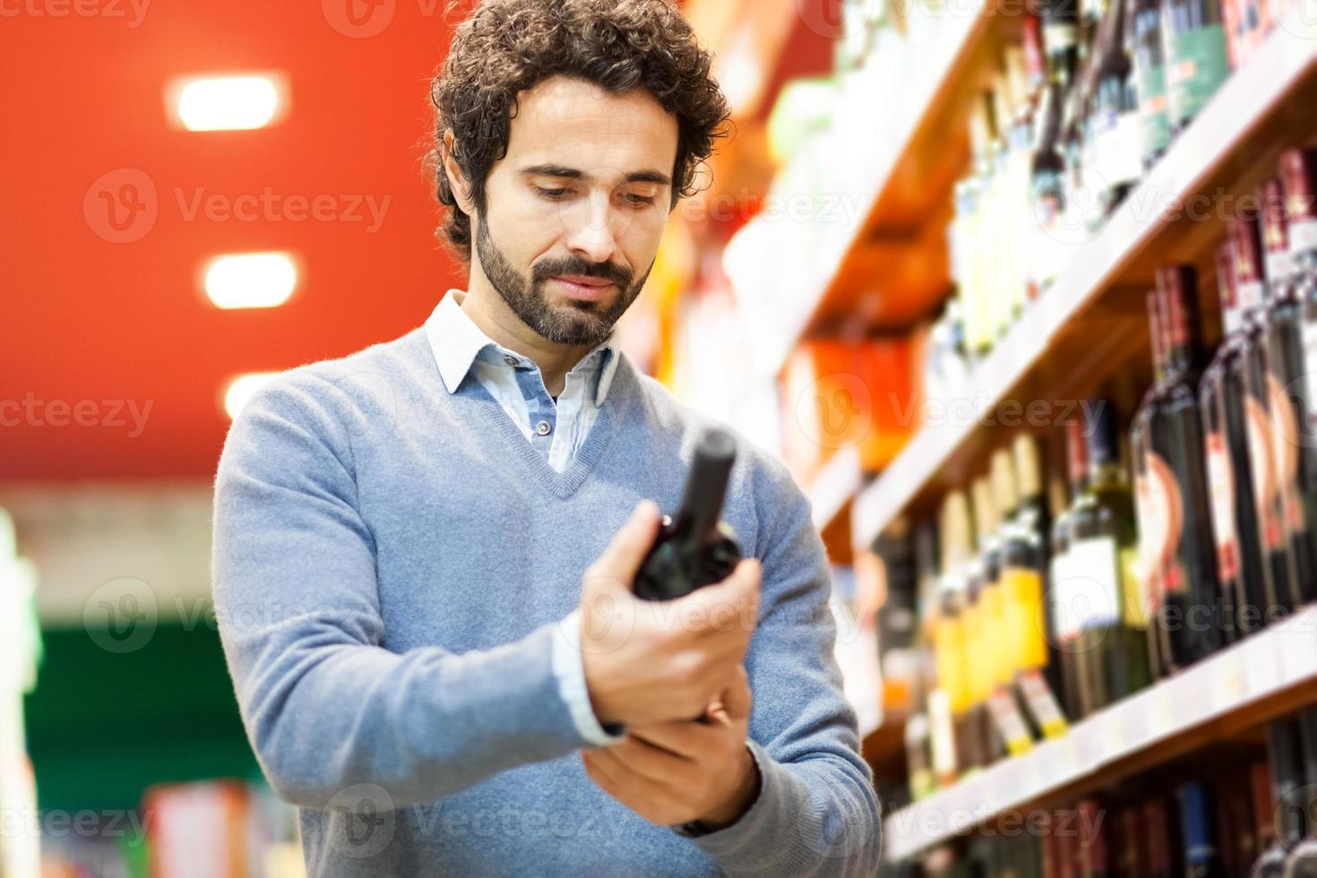 homem em um supermercado, escolhendo a garrafa de vinho foto