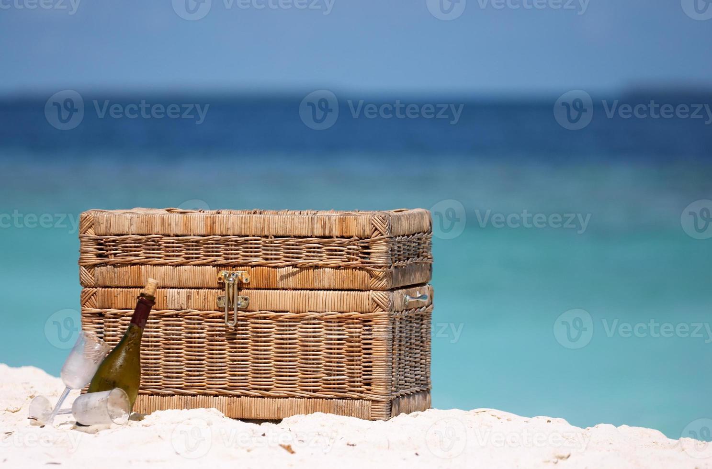 cesta de piquenique em uma praia com o mar ao fundo foto