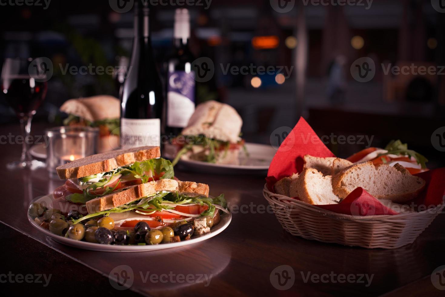 Cena de jantar com vinho, pão branco e sanduíches foto