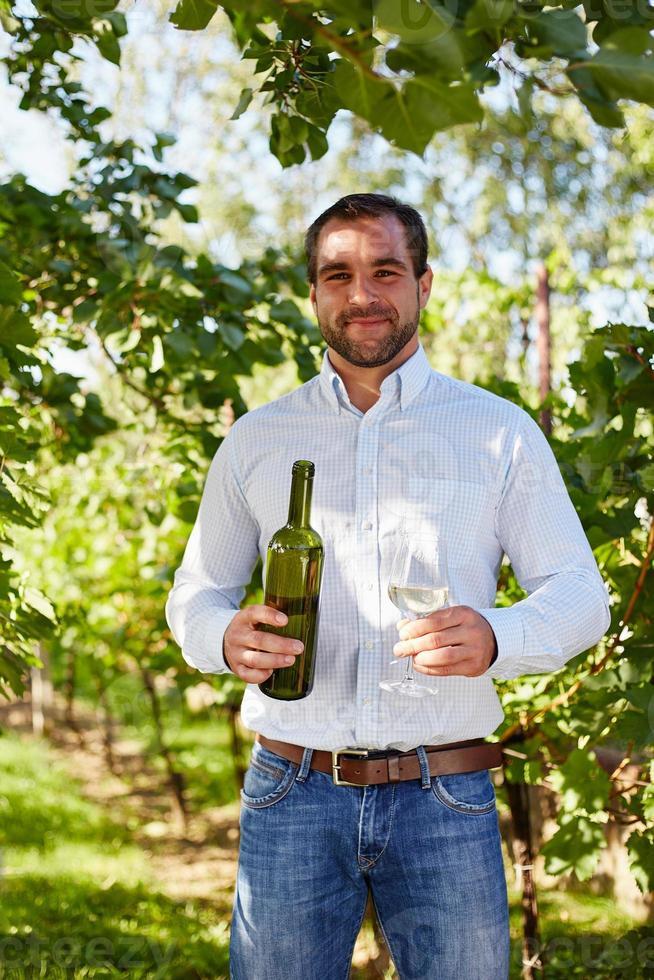 homem com uma taça de vinho branco na vinha foto
