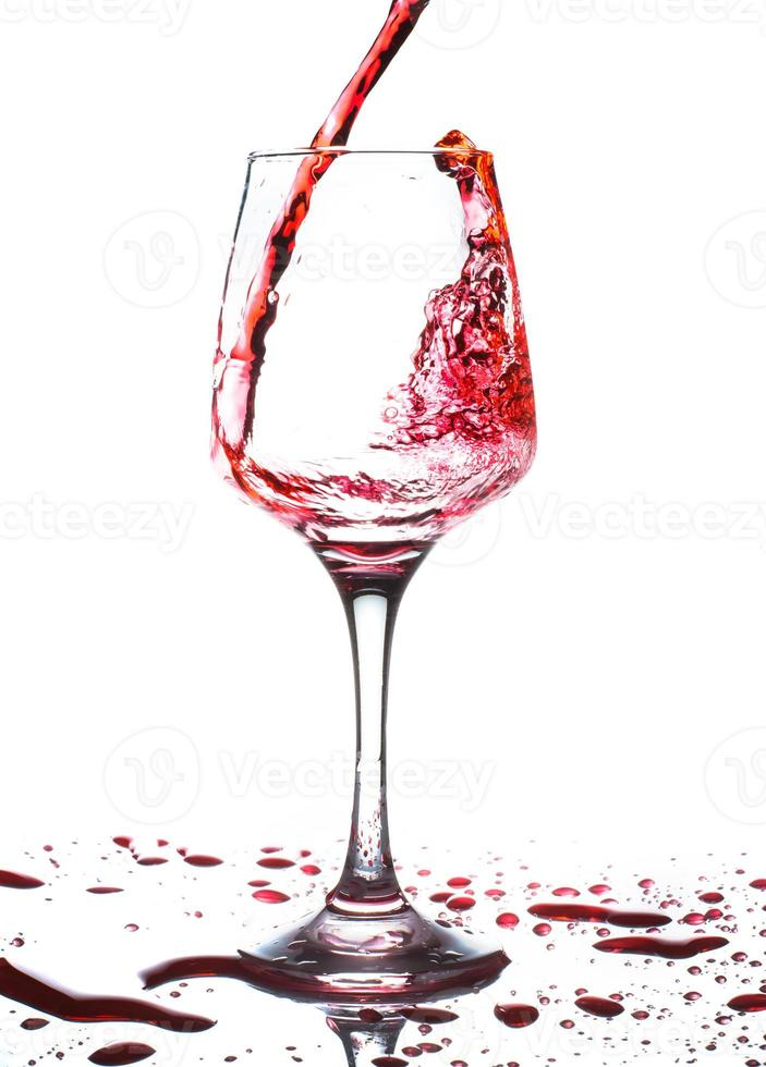 vinho tinto derramando em uma taça de vinho foto